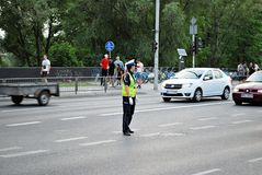 Female police officer controls car traffic. Warfsaw, Poland. June 10, 2017.  Female police officer controls car traffic before the match Poland-Romania Stock Images