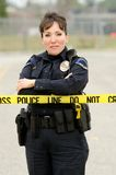 Crime Scene. A female police officer standing behind crime scene tape with her arms crossed stock photos
