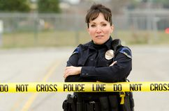 Crime Scene. A female police officer standing behind crime scene tape with her arms crossed stock photo