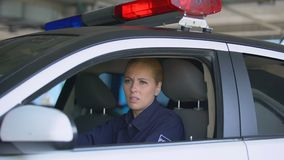 Female police officer taking off sunglasses and seat belt after night shift. Stock footage stock video