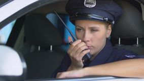 Female police officer transmitting information by radio, patrolling security