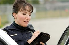 Traffic stop. A female police officer writes a ticket while standing next to her patrol car Royalty Free Stock Photo