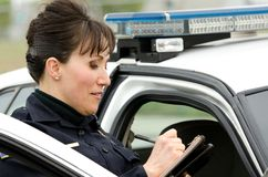 Traffic stop. A female police officer writes a ticket while standing next to her patrol car Royalty Free Stock Images
