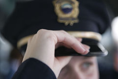 Female police woman's hand adjusting hat. Stock Images