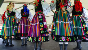Female polish dancers in traditional folklore costumes on stage Stock Photos