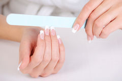 Female polishing her fingernails Royalty Free Stock Images