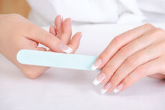Female polishing  her thumb Royalty Free Stock Photo