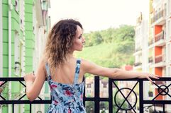 Beautiful slim girl standing on the balcony. She turned her back to the camera and looks to the right. Multicolored old street and royalty free stock photography