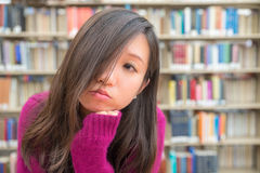 Female Portrait in Library. Close portrait of young woman in library Stock Photo
