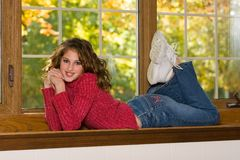 Female Portrait Lying In Window Sill. Happy and spirited portrait of a 12 year old girl on her belly in a window sill Royalty Free Stock Image