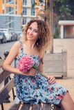 Young beautiful woman is sitting on the bench near the business center. She smiles happily, holds a hydrangea flower in her hands.