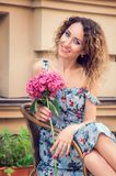 Young beautiful woman sitting in a wicker chair street cafe. She smiles happily, holding a hydrangea flower in her hands. Wearing stock image