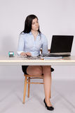 Female poses behind a desk in the office Stock Photos