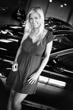 Female posing at line of new cars. Blond young woman posing inside at car dealership Royalty Free Stock Photo