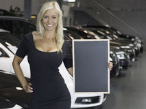 Female posing with sign in front of new cars. Young blond smiling female holding board at a car dealership with luxury cars Royalty Free Stock Photos