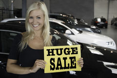Female posing with sign in front of new cars. Young blond smiling female holding sign with huge sale text at a cardealership Royalty Free Stock Image