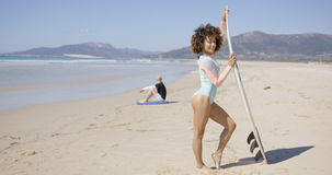 Female posing with surfboard on beach Stock Photo
