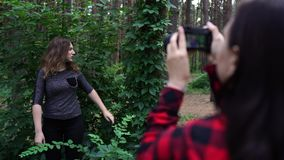 Female posing for a woman photographer in the forest stock video footage
