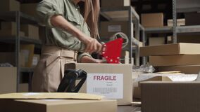 Female post mail storage worker holding tape dispenser sealing shipping box.