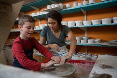 Female potter assisting boy in molding a clay Stock Photo
