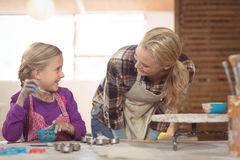 Female potter assisting girl in painting Stock Photography