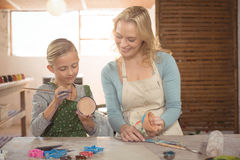 Female potter assisting girl in painting Stock Photo