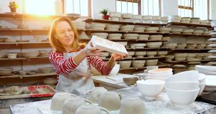 Female potter checking craft product 4k. Female potter checking craft product in pottery workshop 4k stock video footage