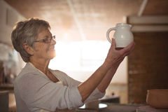 Female potter checking jug Royalty Free Stock Images
