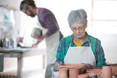 Female potter checking pots Royalty Free Stock Photography