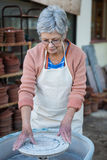Female potter checking pottery wheel Royalty Free Stock Photos