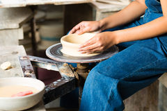 Potter creating clay bowl on turning wheel Royalty Free Stock Image