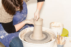 Female Potter creating a earthen jar on a Potter's wheel Royalty Free Stock Photos