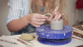 Ceramist woman is fixing handle to clay cup in workshop, close-up. Female potter is fastening a knob to ceramic bowl in working studio. She is producing handmade stock video footage