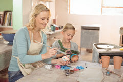 Female potter and girl painting in pottery workshop Royalty Free Stock Photography