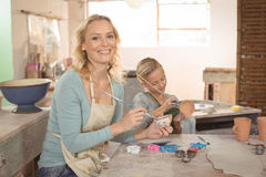 Female potter and girl painting in pottery workshop Royalty Free Stock Photos
