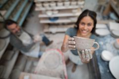 Female potter holding clay cup Stock Photo