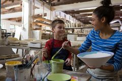 Female potter interacting with boy while painting bowl Royalty Free Stock Photo