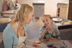Female potter interacting with girl in pottery workshop Stock Images