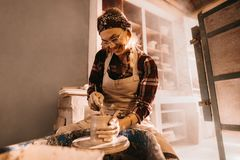 Female potter making clay pot. Woman potter making a clay pot on pottery wheel in workshop. Craftswoman moulding clay with a stick on pottery wheel Royalty Free Stock Photo
