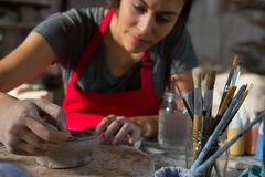 Female potter molding a bowl with hand tool Stock Photo