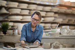 Female potter molding plate with hand tool Royalty Free Stock Photos