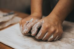 Female potter works with clay, craftsman hands close up, kneads and moistens the clay before work stock photos