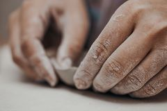 Female potter works with clay, craftsman hands close up, kneads and moistens the clay before work stock photo