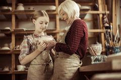 Female potters in aprons holding clay vase standing at workshop Royalty Free Stock Images