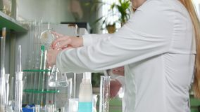 A female pour liquid from one flask to another stock footage