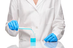 Female pouring blue liquid from test tube into measuring cup Royalty Free Stock Photos