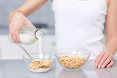 Female pouring milk in plate with oak flakes. Stock Photos