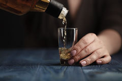 Female pouring whiskey in to glass shot Stock Image