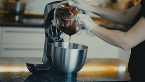Female pours from a transparent bowl sweet syrup in a bowl kneaders. stock video