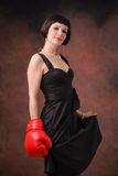 Female power. A young beautiful female posing with a boxing gloves Stock Image